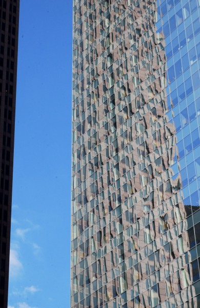 A center city building appears to be shedding its rough and mottled skin for a smoother one; Philadelphia, Pennsylvania, USA.  April 2009.