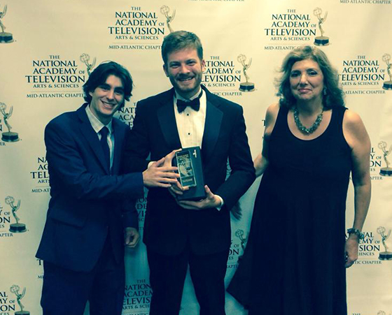 Faculty Advisor Fran Viola stands with student producers holding their Emmy award